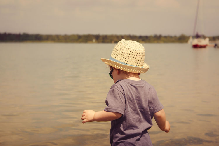 Boy wearing hat while standing at beach