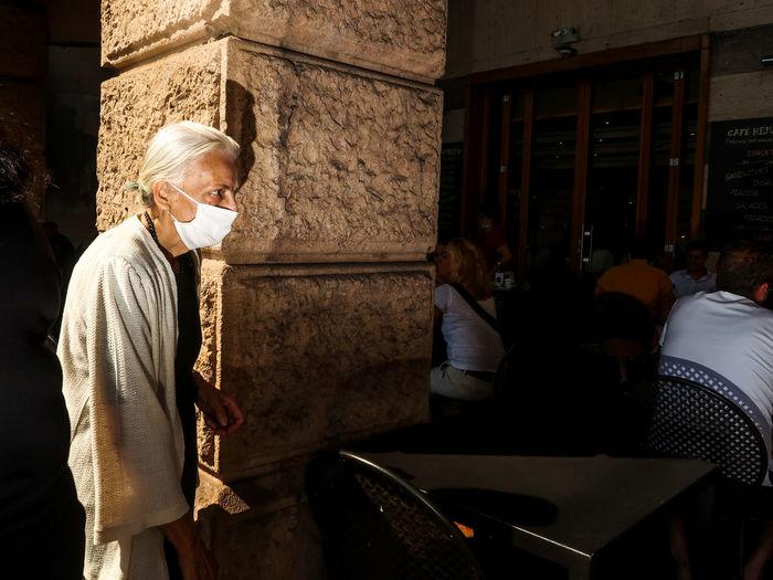 Senior woman wearing mask standing at restaurant