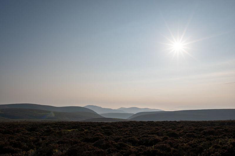 Scenic view of landscape against bright sun