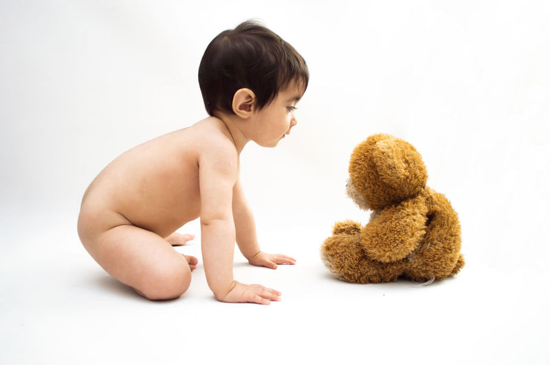 Side view of shirtless boy against white background