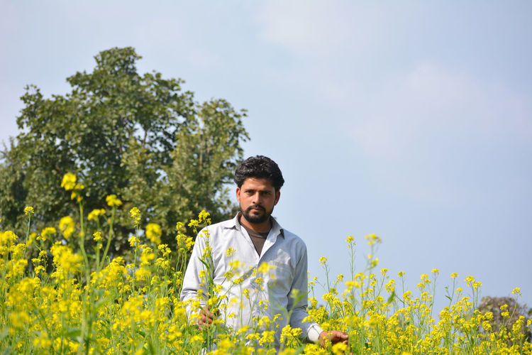 Young man with yellow flowers in field