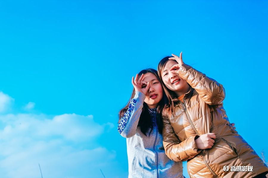Sister Blue Togetherness Smiling Outdoors Happiness Fun Fashion Stories Lifestyles Two People Real People Young Adult Friendship Cheerful Sky Leisure Activity Day Women Low Angle View Piggyback Arm Around Females