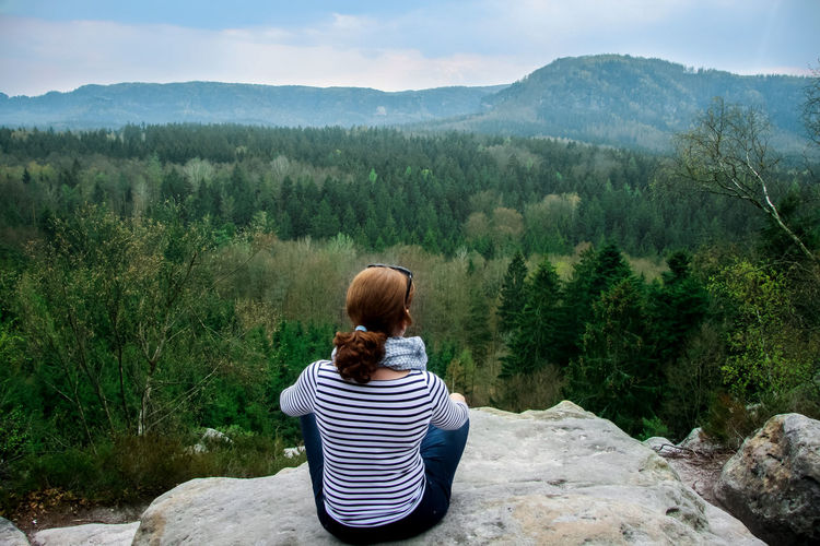 Rear view of woman sitting on mountain