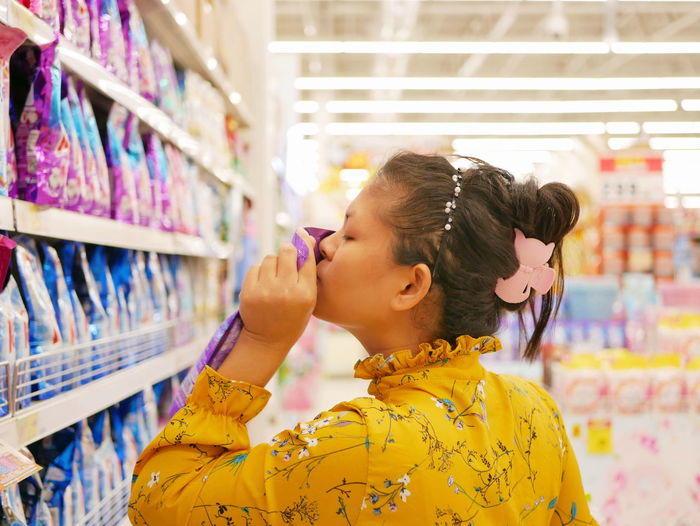 Woman smelling packet in supermarket
