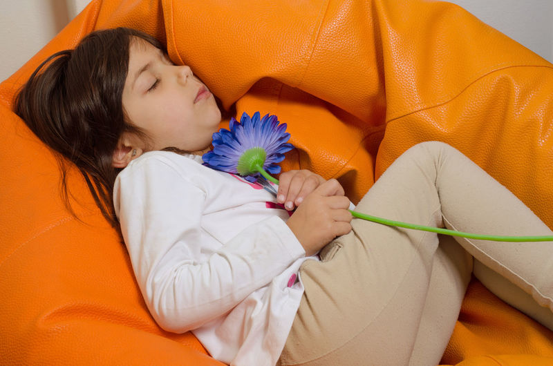 High Angle View Of Girl Holding Flower While Sleeping On Bean Bag