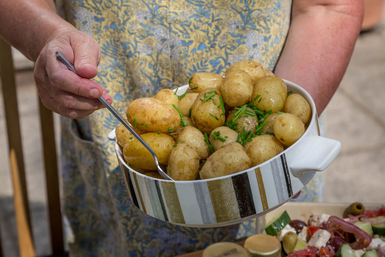 Midsection Of Woman Preparing Potatoes At Home