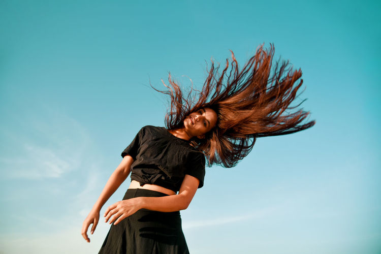 Low angle view of woman tossing hair against clear sky