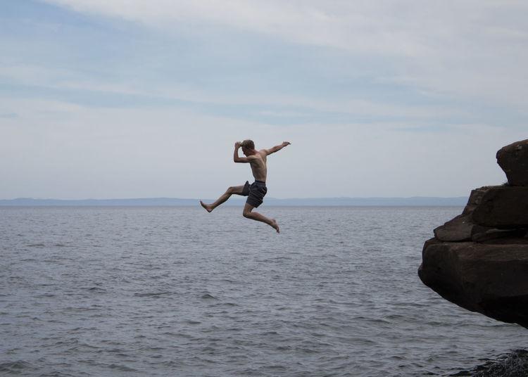 Full length of man jumping in sea against sky