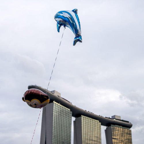 Low Angle View Of Helium Balloons Flying Against Marina Bay Sands