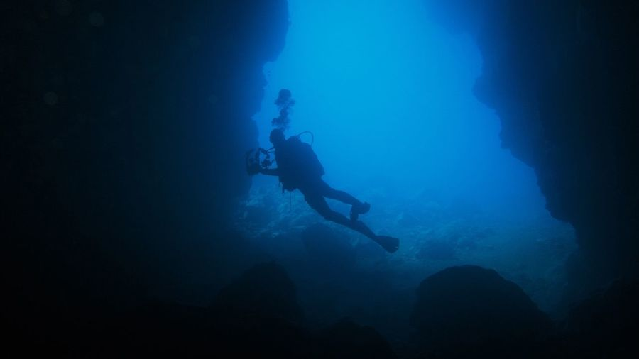 Silhouette person scuba diving undersea