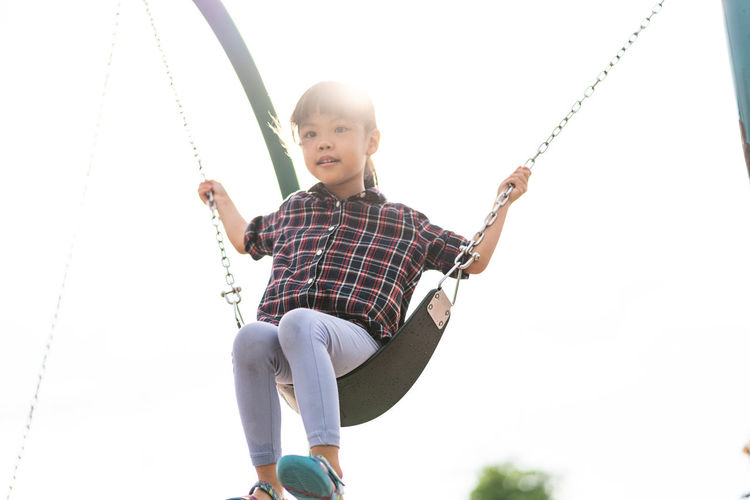 Asian little girl playing swing at playground Portrait Happy Holiday Summer Rope Swing Child Childhood Smiling Happiness Cheerful Playing Swing Girls Fun Playground