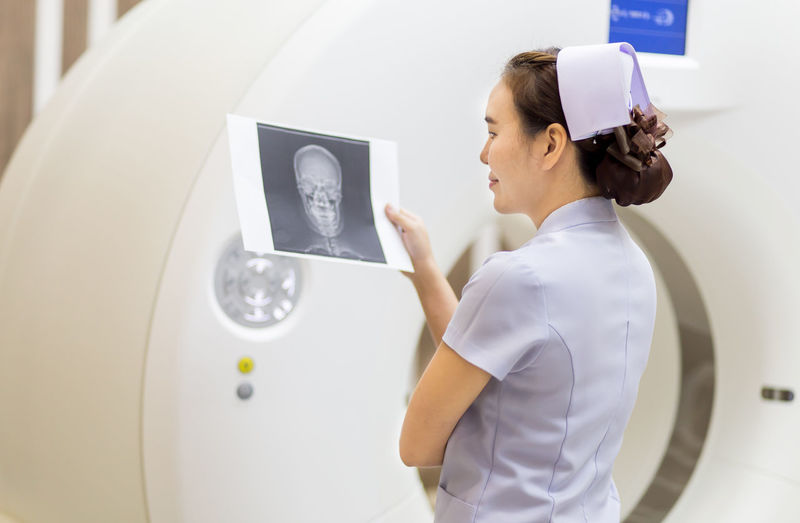 Nurse Looking At X Ray While Standing In Hospital
