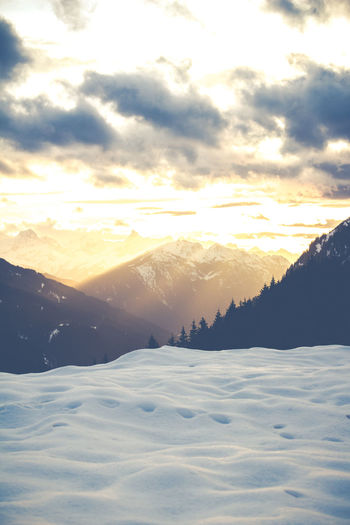 Scenic view of snow mountains against sky during sunset