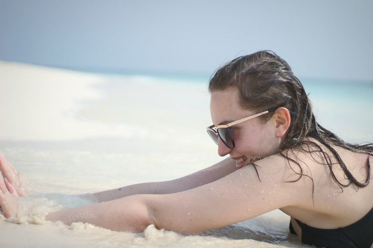 Side View Of Smiling Mid Adult Woman Lying On Beach