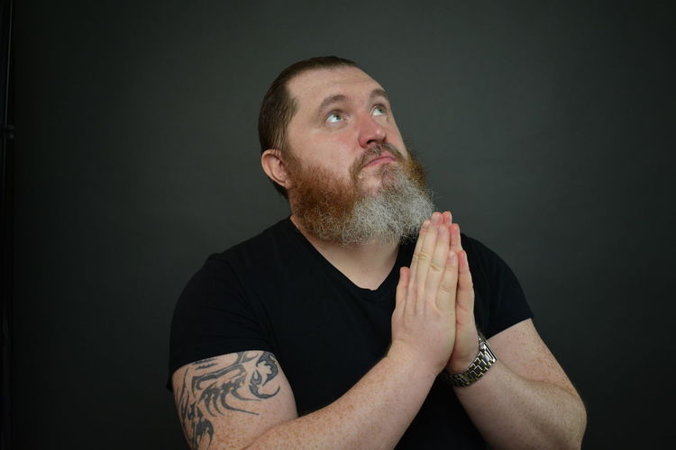 Portrait of man looking away against black background
