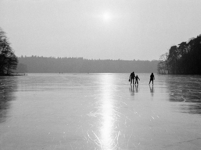 Family On Frozen Lake Against Sky
