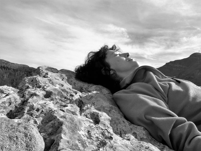 Woman Lying Down On Rock Against Sky