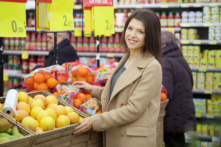 Portrait Of Smiling Young Woman Standing By Fruits In Store