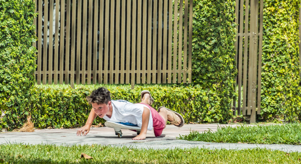 Casual Clothing Childhood Day Front Or Back Yard Grass Happiness Healthy Eating Hot Kid Leisure Activity Lifestyles Lying Down Men Outdoors People Playing Outside Relaxation Sitting Skateboard Skateboarding Smiling Summer Sunshine Tree