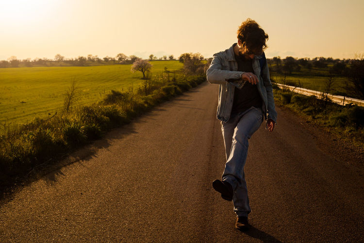 Man walking on road amidst land against sky during sunset
