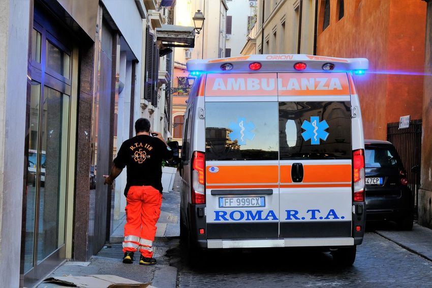 Rome, Italy - August 15, 2017: Italian Emergency Mobile Unit. Back turned paramedic next to an ambulance parked in a narrow street in Rome 118 Doctor  Emergency First Aid Medicine Paramedic Ambulance Ambulance Service Ambulance Staff Cure Emergency Services Healthcare And Medicine Medical Narrow Street One Person Outdoors People Real People Safety Vehicle