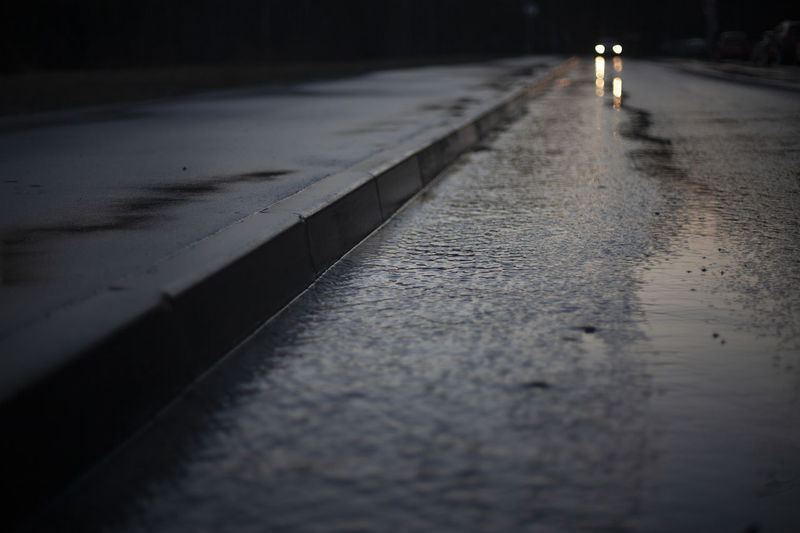 Car headlights in the distance. road on a rainy day. a puddle on the highway.