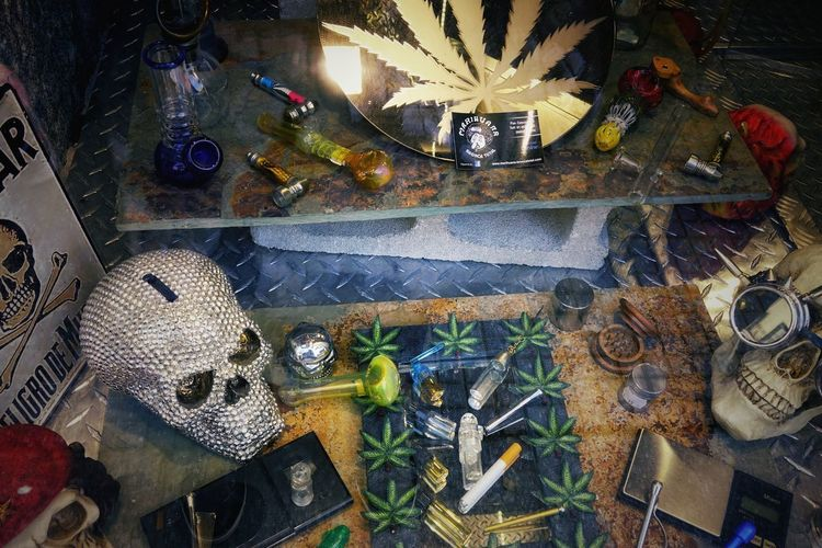 Rastafari Reggae Cannabis Pipe Pipe - Tube Lifestyle Madrid Rastro Reflection SPAIN Shopping Window Shopping Art And Craft Choice Decoration Decorations Glass - Material Large Group Of Objects Lifestyles Marijuana No People Rock Music Scull Shop Store Store Window Tool Variation Variety Window Display