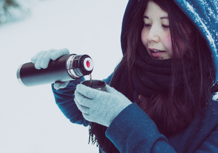 Close-Up Of Woman With Thermos In Snow