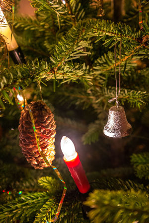 Close-up of a bright red candle, decorative bell and cone hanging on a Christmas tree Christmas Christmas Spirit Christmas Time! Christmas Bell Fir Branch Green Color Light Celebration Christmas Candle Christmas Decoration Christmas Ornament christmas tree Close-up Cone Hanging No People Plant Tree