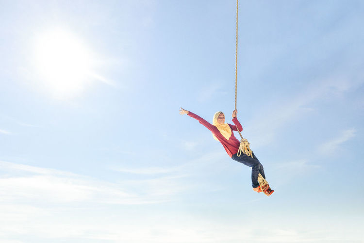 Low angle view of carefree teenage girl standing on rope against sky