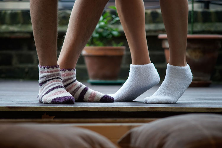 Low section of couple wearing socks at patio