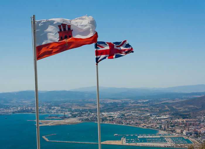 Union Jack flag and Gibraltar flags blowing in the wind in Gibraltar Flag Patriotism Water Cityscape Wind Pride Waving Day National Icon Flags In The Wind  Flags Flag Pole Flag Poles Union Jack Gibraltar Flag Gibraltar Flag And Union Jack Gibraltar Gibraltar Views British Outdoors Sky