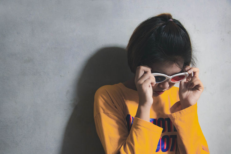 Woman wearing sunglasses against wall