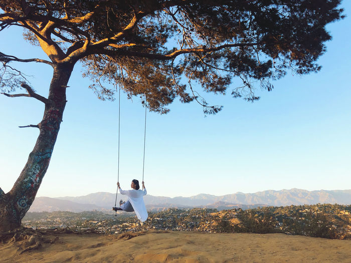Rear view of woman swinging over on mountain against sky