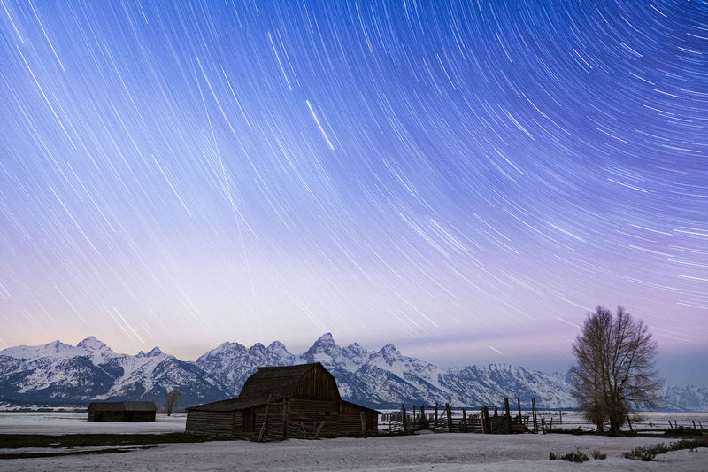 Barn on snow covered field against star trails at dusk