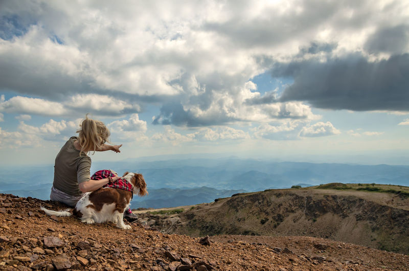 Woman and her dog, cavalier king charles spaniel, on a mountain top watching a picturesque landscape