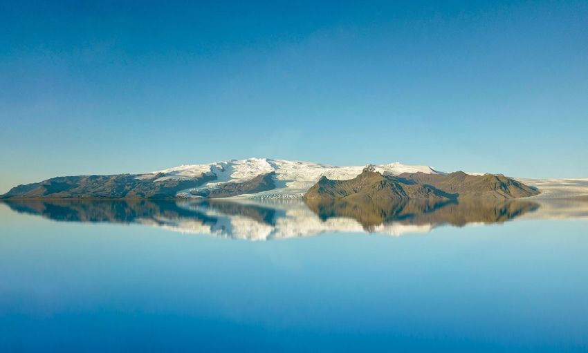 Beautiful scenery of mountains in iceland with blue sky and water reflection.