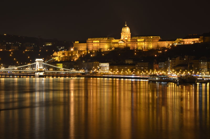 Illuminated Buda Castle By Danube River Against Sky In City At Night