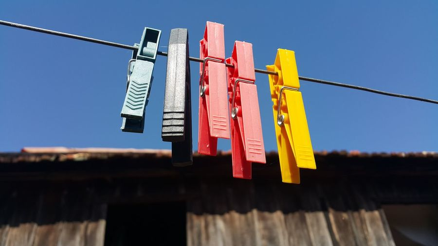 Low Angle View Of Clothes Pegs Against Blue Sky
