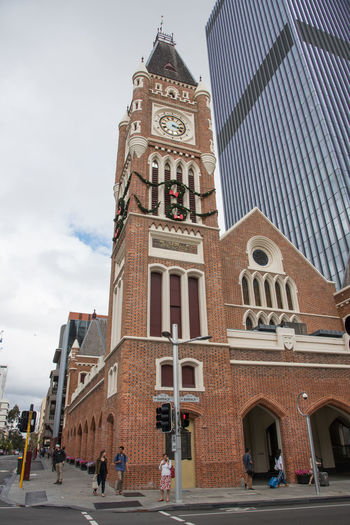 Old brick building with clock tower and tourists on street corner in Perth, Western Australia. Arch Architecture Brick Building City City Life Clock Cloudy Corner Façade Lifestyle Moody Sky Overcast Pedestrian Perth Real People Sidewalk Street Street Corner Tourists Tower Travel Destinations Urban Walking Western Australia