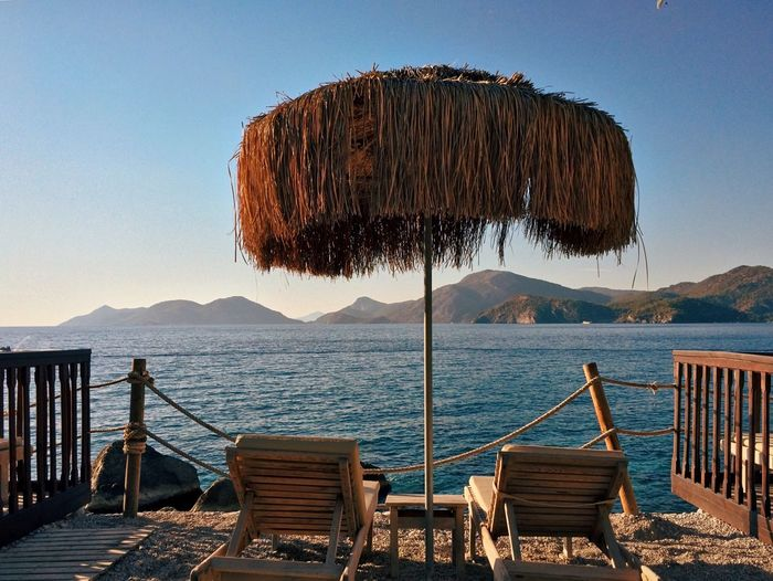 Chair Mountain Water Sea Thatched Roof Outdoors Clear Sky No People Beach Relaxation Beauty In Nature Day