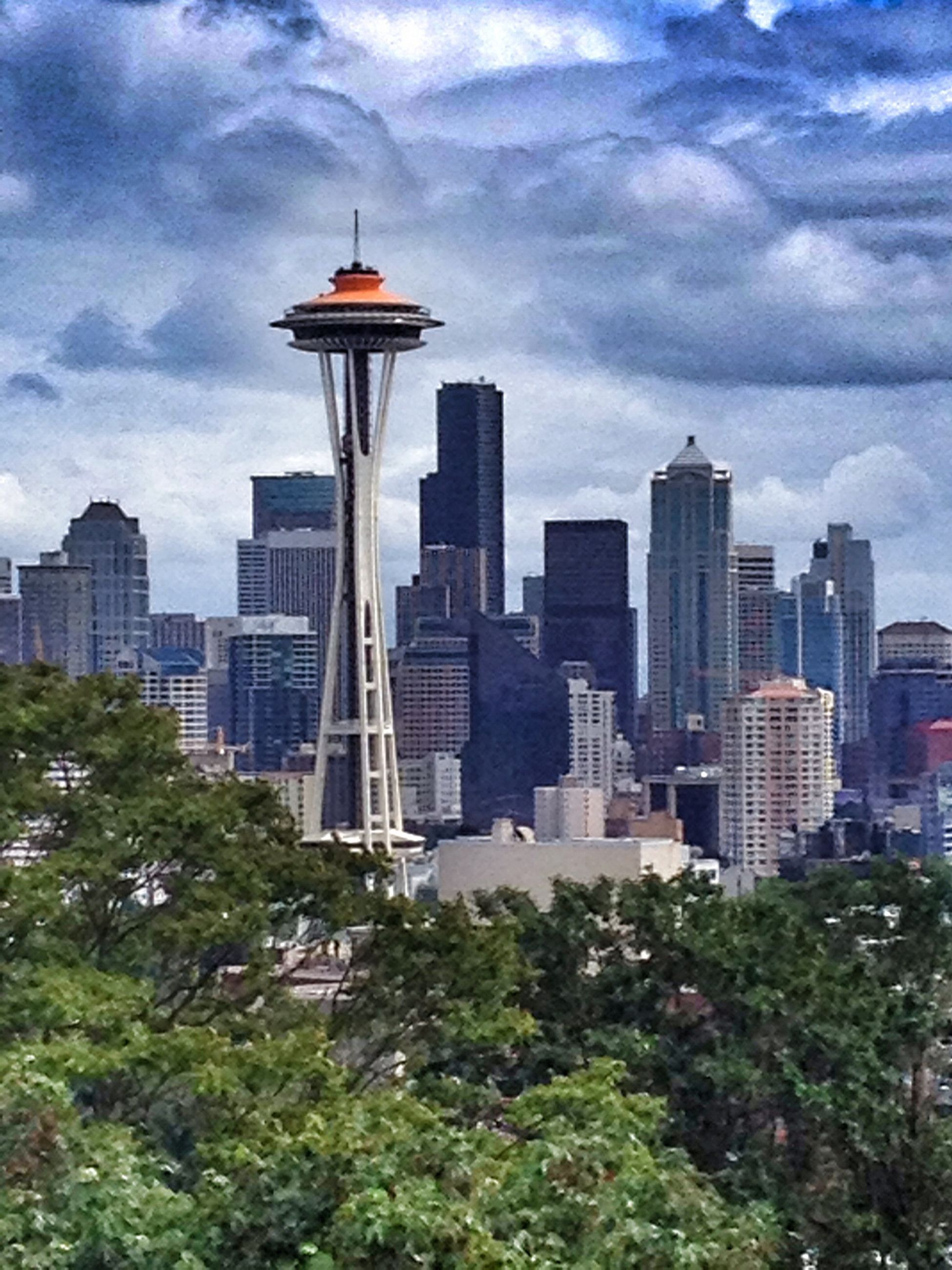 building exterior, architecture, city, built structure, skyscraper, tower, tall - high, sky, modern, cityscape, cloud - sky, office building, tree, urban skyline, capital cities, cloud, growth, cloudy, financial district, travel destinations