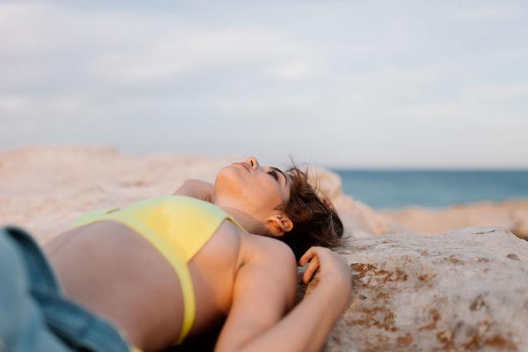 Woman lying on beach against sky
