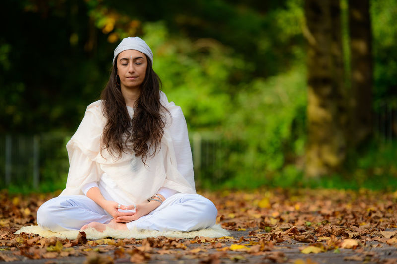Full length of woman meditating on land outdoors
