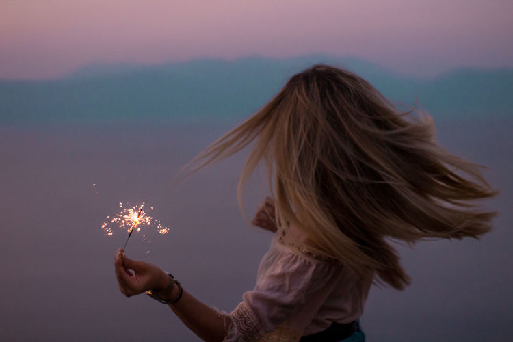 Woman holding sparkler against sky during sunset