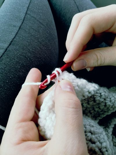 Midsection of woman crocheting wool