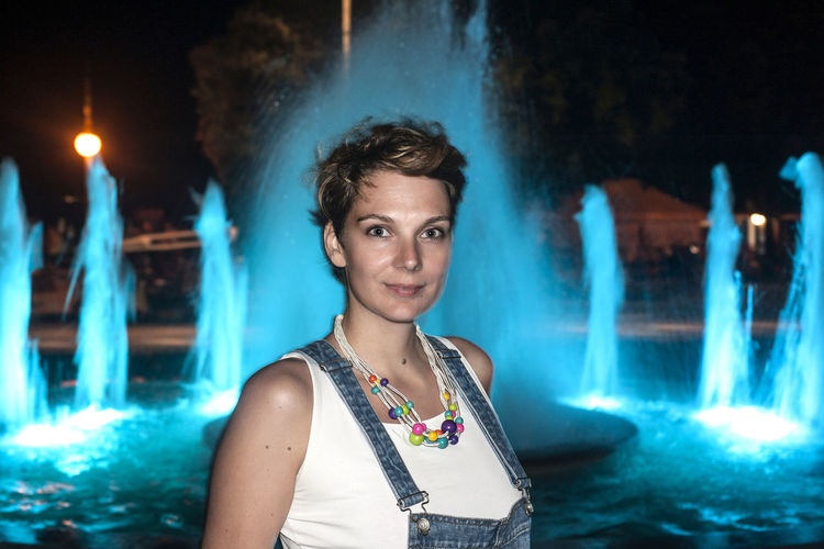 Portrait of woman against blue waterfall at night