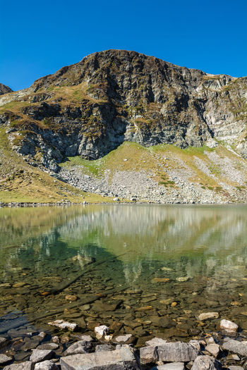Seven Rila lakes, Bulgaria; The Kidney Бъбрека (Babreka) 2,282 m (7,487 ft) 8.5 ha (21 acres) 28.0 m (91.9 ft) Mountain Water Beauty In Nature Tranquility Tranquil Scene Scenics - Nature Rock Lake Sky Day Non-urban Scene No People Nature Rock - Object Solid Idyllic Reflection Mountain Range Clear Sky Outdoors Formation Lake View Lakeside Lakeshore Nature