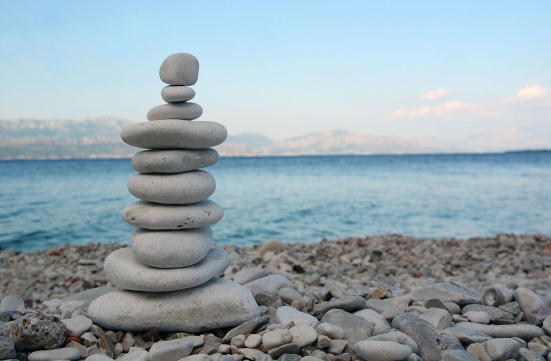 Stack of pebbles by sea against sky