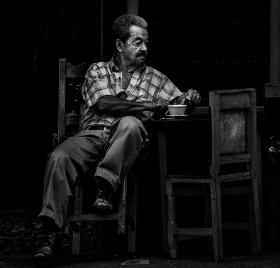 Man Having Tea While Sitting On Chair